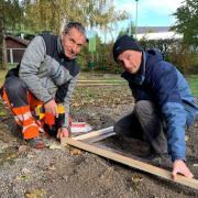 Im Illertisser Ortsteil Betlinshausen wird der Spieplatz am Vereinsheim erneuert. Michael Kremmeter (links) und Michael Kienast vom Bauhof legen den Grundriss für ein neues Haus zum Spielen.