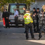 Ein Bestatter, Mitarbeiter des Deutschen Roten Kreuzes und Polizisten stehen am Sonntag vor dem Tatort im Münchner Stadtbezirk Bogenhausen. Hier ist ein 14-jähriges Mädchen tot aufgefunden worden.