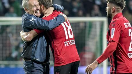 Freiburgs Coach Christian Streich gratuliert seinem Doppeltorschützen Nils Petersen. Foto: Axel Heimken/dpa