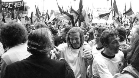Durch jubelnde Fans bahnen sich (M-r) Günter Netzer, Herbert Wimmer und Horst-Dieter Höttges ihren Weg.
