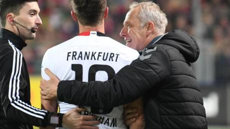 Freiburgs Trainer Christian Streich (r) umarmt Frankfurts David Abraham (l). Foto: Patrick Seeger/dpa