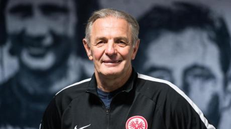 Karl-Heinz «Charly» Körbel steht vor einer Wand mit den Porträts ehemaliger Eintrachtspieler.