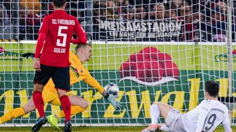 Mit seinem 221 Bundesliga-Tor brachte Robert Lewandowski (r) den FCBayern in Freiburg in Führung.