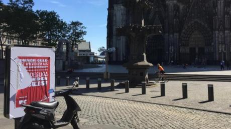 Ein halb abgerissenes Plakat hängt an einer Werbefläche vor dem Kölner Dom.