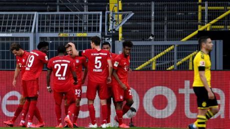 Die Bayern-Spieler feiern in Dortmund den Matchwinner Joshua Kimmich (M).