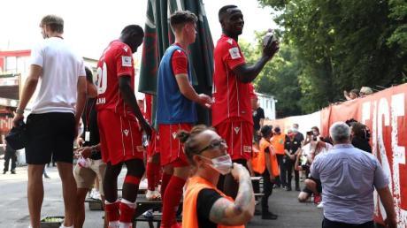 Spieler von Union Berlin feiern mit Fans auf der anderen Seite des Zauns am Stadion An der alten Försterei.