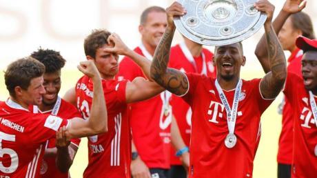 Thomas Müller feiert mit seinen Teamkameraden und Meisterschale.