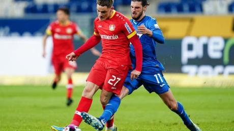 Leverkusens Florian Wirtz schirmt den Ball im Zweikampf mit Hoffenheims Florian Grillitsch (r) ab.