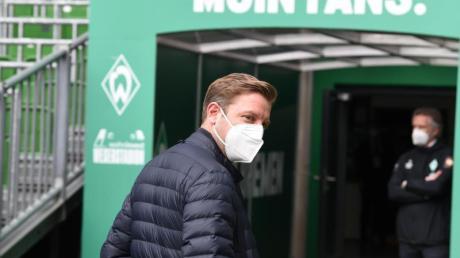 Werders Trainer Florian Kohfeldt (l) geht aus dem Innenraumbereich in die Kabine, im Hintergrund steht Geschäftsführer Frank Baumann.