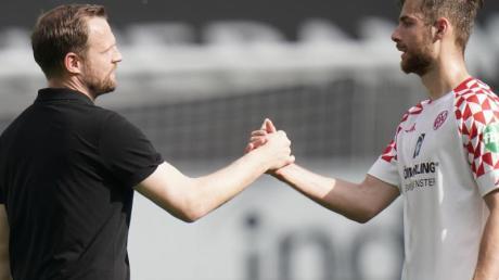 Mainz-Trainer Bo Svensson (l) klatscht nach dem Spiel mit Abwehrspieler Alexander Hack ab.