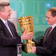 DFB-Präsident Reinhard Grindel (l) übergibt den DFB-Pokal an Berlins Regierenden Bürgermeister Michael Müller.
