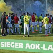 Die Cottbusser beobachten nach dem Pokalsieg die Pyroaktionen der Babelsberger Fans. Die Siegerehrung wurde abgebrochen. Foto: J. Kuppert