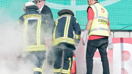 Feuerwehrleute löschen brennende Bengalos, die von Mainzer Fans aufs Spielfeld geworfen wurden.