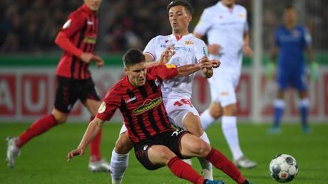 Freiburgs Roland Sallai (l) und Unions Nicolai Rapp lieferten sich mit ihren Teams einen packenden Pokalfight.