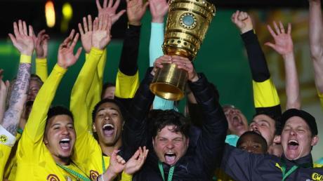 BVB-Coach Edin Terzic streckt den DFB-Pokal in den Berliner Nachthimmel.