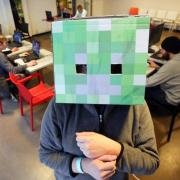 """Ein Teilnehmer des Computer-Festivals play13 in Hamburg mit einem aus Pappe nachgebauten Würfel des Computerspiels """"Minecraft"""". Foto: Bodo Marks"""