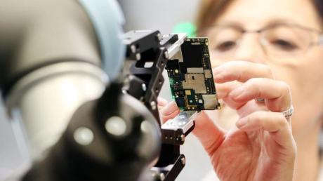 Eine Gigaset Mitarbeiterin und ein Roboter montieren das Smartphone GS 185 von Gigaset in Bocholt.