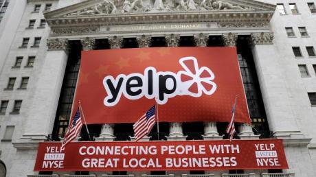 Ein Banner mit dem Logo des Bewertungsportals Yelp hängt am Gebäude des New York Stock Exchange in New York. Foto: Justin Lane/EPA/Archiv