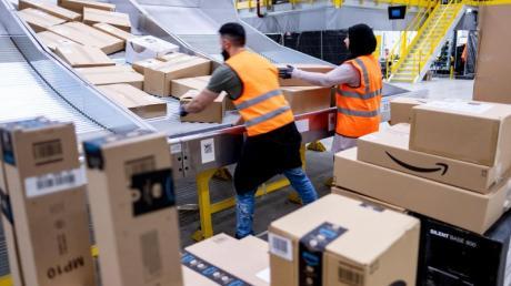 Mitarbeiter des Paketversenders Amazon sortieren Pakete im Sortierzentrum in Garbsen.