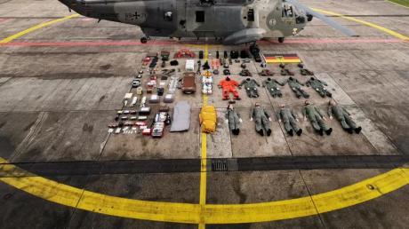 Fünf Seenotretter samt Ausrüstung liegen neben dem Rettungshelikopter SeaKing MK41.