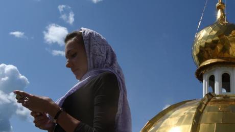 Eine Frau schaut auf dem Dach der orthodoxen Kathedrale von St. Theodor Uschakow in Saransk, Russland, auf ihr Smartphone. Foto: Marcus Brandt/dpa