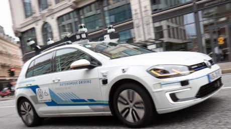 Ein Elektro-Golf, bestückt mit Laserscannern, Kameras, Ultraschallsensoren und Radar für vollautomatisches Fahren, ist bei einer Testfahrt in der Innenstadt unterwegs.
