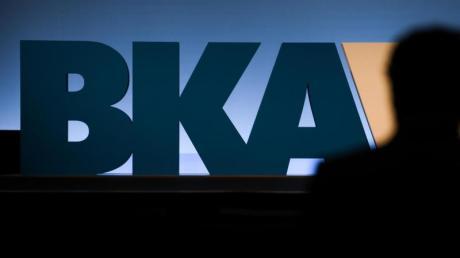 Auf einer Bundeskriminalamt-Tagung steht ein Mann vor dem BKA-Logo der Behörde.