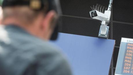 Ein Reisender steht vor einer Überwachungskamera, die während einer Testphase zur Gesichtserkennung im Bahnhof Südkreuz zu sehen ist.