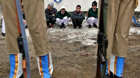Indische Soldaten vor Schülern aus Kaschmir während einer Parade zum indischen Nationalfeiertag.