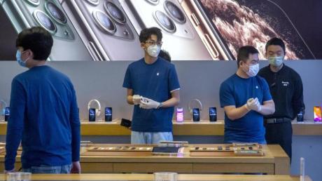Dieser Apple-Store in Peking hat zwar wieder geöffnet, die Mitarbeiter schützen sich aber trotzdem weiter mit Mundschutz und Handschuhen.