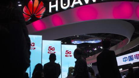 Besucher gehen an einem Display für 5G-Dienste des chinesischen Technologieunternehmens Huawei auf der PT Expo in Peking vorbei.