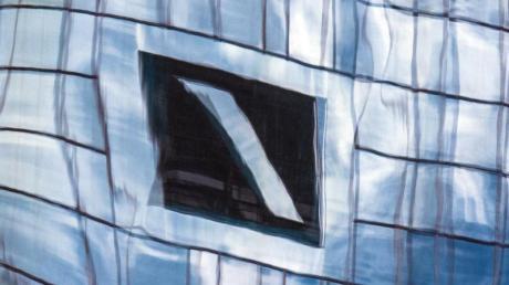 Die Zentrale der Deutschen Bank in Frankfurt am Main spiegelt sich in einer Glasfassade.