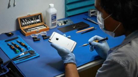 Ein Service-Techniker arbeitet an einem iPhone.