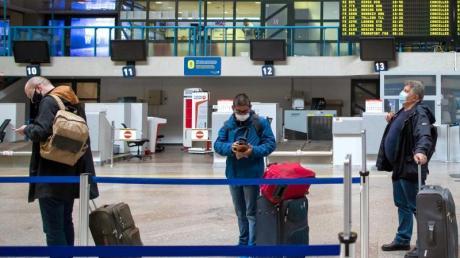 Passagiere mit Smartphones in einer Schlange im Internationalen Flughafen von Vilnius.