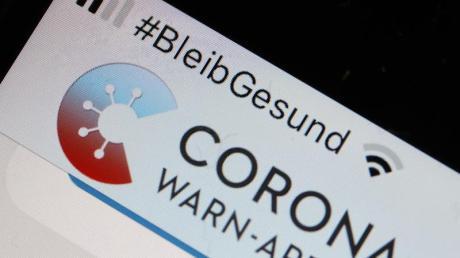 Die Corona-Warn-App mit der Seite zur Risiko-Ermittlung ist im Display eines Smartphone zu sehen.