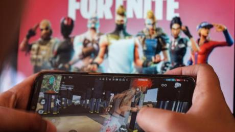 Ein Kind spielt ein Spiel auf einem Mobiltelefon mit einem Bild des Fortnite-Spiels auf dem Computerbildschirm im Hintergrund. Kalifornien.