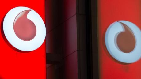 Das Logo von Vodafone spiegelt sich in der Fensterscheibe einer Verkaufsfiliale des Unternehmens.