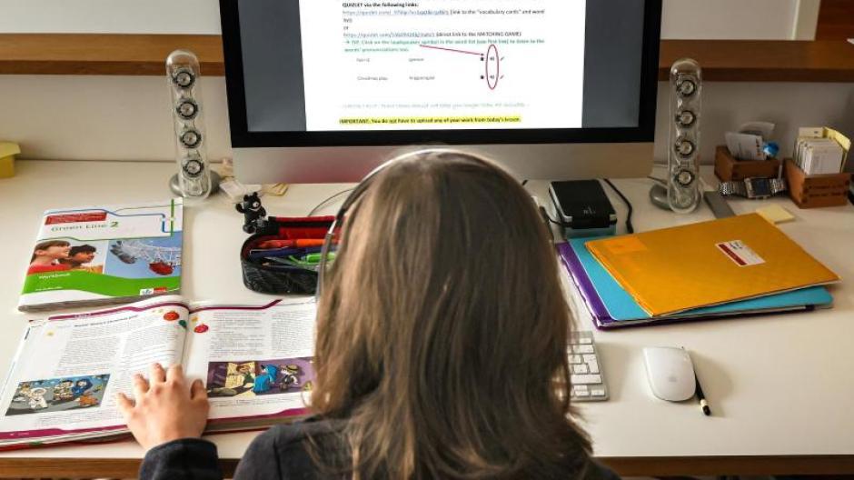 Ein zwölfjähriger Gymnasiast löst am Computer in seinem Zuhause seine Schulaufgaben, die ihm seine Lehrer für jeden Tag über den Schulserver geschickt haben.