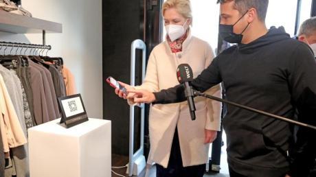 Ministerpräsidentin Manuela Schwesig (l.) von Tom Pantel, Geschäftsinhaber, im Modegeschäft Compromis Label & Lounge das einchecken mit der Luca-App erklären.