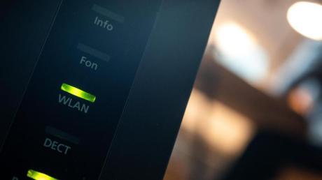 Ein Router, auf dem die LED für W-Lan und DSL leuchten, ist in einer Wohung zu sehen.