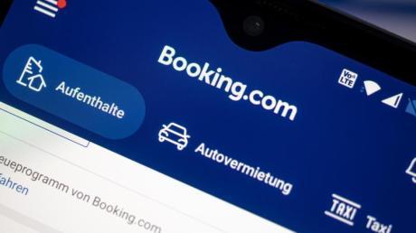 Auf einem Smartphone ist die App des Reiseportals Booking.com zu sehen.