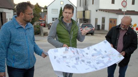 Die beiden Diplomingenieure Beckert (links) und Kimmerle (Mitte) erklären den Gemeinderatsmitgliedern anhand eines Plans den aktuellen Sachstand bei den Tiefbaumaßnahmen in der Ziegeleistraße und Am Anger in Finningen.