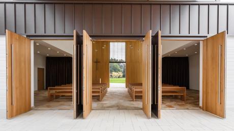 Das Foto zeigt, wie die Halle bei geöffneten Türen für eine große Gruppe Trauernder genutzt werden kann. Die Schiebetür am hinteren Ende führt direkt zum Friedhof, sodass der Weg des Sarges immer in die gleiche Richtung verläuft.