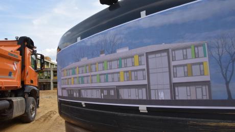 Die Erdarbeiten haben beim Bau der neuen Dillinger Mittelschule bereits begonnen. Auf dem Bagger ist zu sehen, wie das Gebäude ausschauen soll.