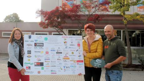 """Viele Menschen und Unternehmen haben für den """"Herzplatz"""" gespendet. Sie werden jetzt auf der Tafel genannt, die (von links) Quartiersmanagerin Ulla Seeßle, Bürgermeisterin Katja Müller und Bauhofleiter Josef Mang präsentieren."""