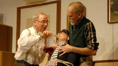 Opa Sebastian Nägele (links) flößt mit seinem Spezi, dem altledigen Bauern Fidel (rechts), dem ambitionierten Geigenlehrer seiner Enkelin Brigitte namens Baldouin seinen Selbstgebrannten ein.