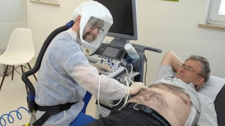 Allgemeinarzt Georg Kügel untersucht einen fiktiven Patienten mit dem Lungenultraschallgerät. Dank seiner selbst entwickelten Haube zur Behandlung von Patienten mit Covid-19-Symptomen ist er von FFP-Schutzmasken unabhängig.