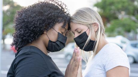 Zwei junge Frauen mit Mund-Nase-Schutz in einem innigen Moment. Am Montag beginnt die internationale Woche gegen Rassismus.