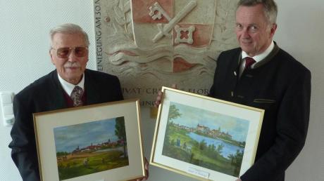 Rudolf Grabmair (links) übergab Bürgermeister Gerhard Pfitzmaier zwei von ihm gemalte Ansichten von Donauwörth und Neuburg.
