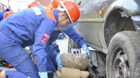 Bei einer Übung versuchen die Jugendlichen einen unter einem Auto eingeklemmten Mann zu befreien – zum Glück ist dieser heute aus Holz.